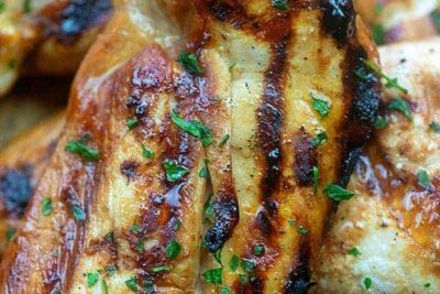 Teryaki covered grilled chicken breast resting on another chicken breast.