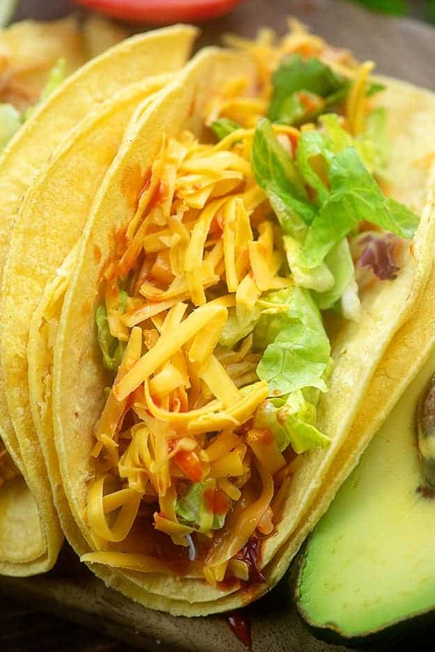 instant pot chicken tacos with cheese and lettuce on corn tortillas