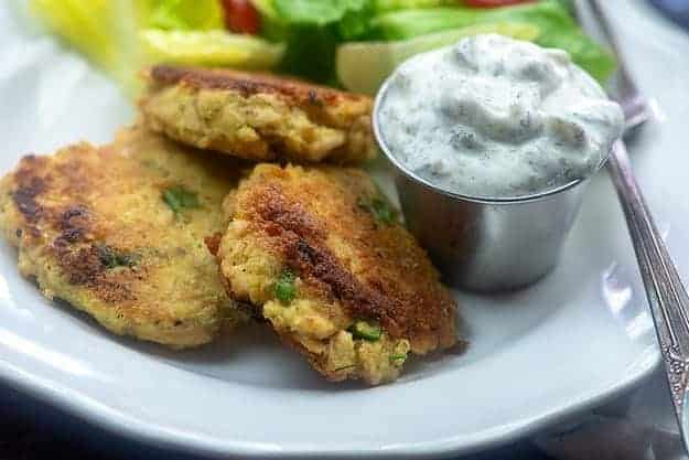 tartar sauce and salmon patties on white plate.
