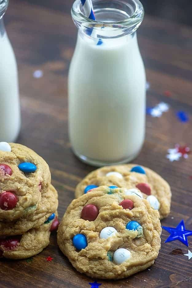 Several M&M cookies with a jar of milk on a table.