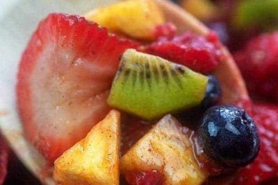 A wooden spoon holding up fruit salad to the camera.