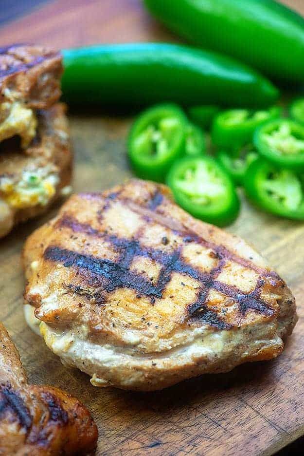 A grilled pork chop on a cutting board with jalapeno peppers in the background.