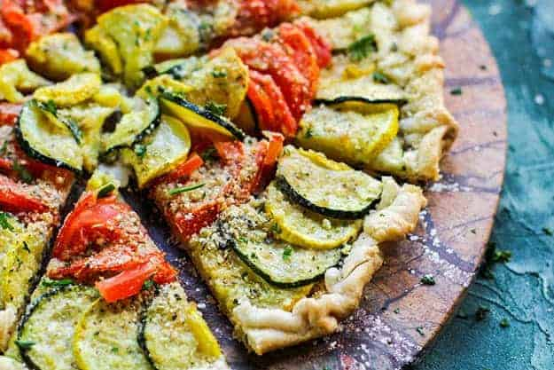 A slice of tomato tart on a pizza paddle.