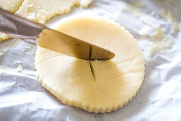 Using a butter knife to cut cookie dough to look like pie crust