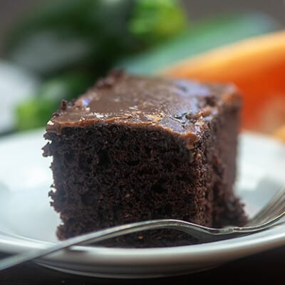 A tall square piece of chocolate cake on a small white plate.