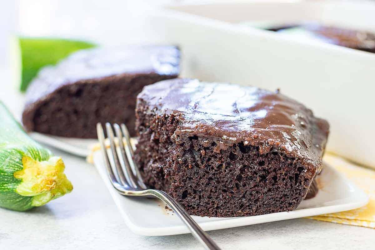 slice of chocolate zucchini cake on white plate.