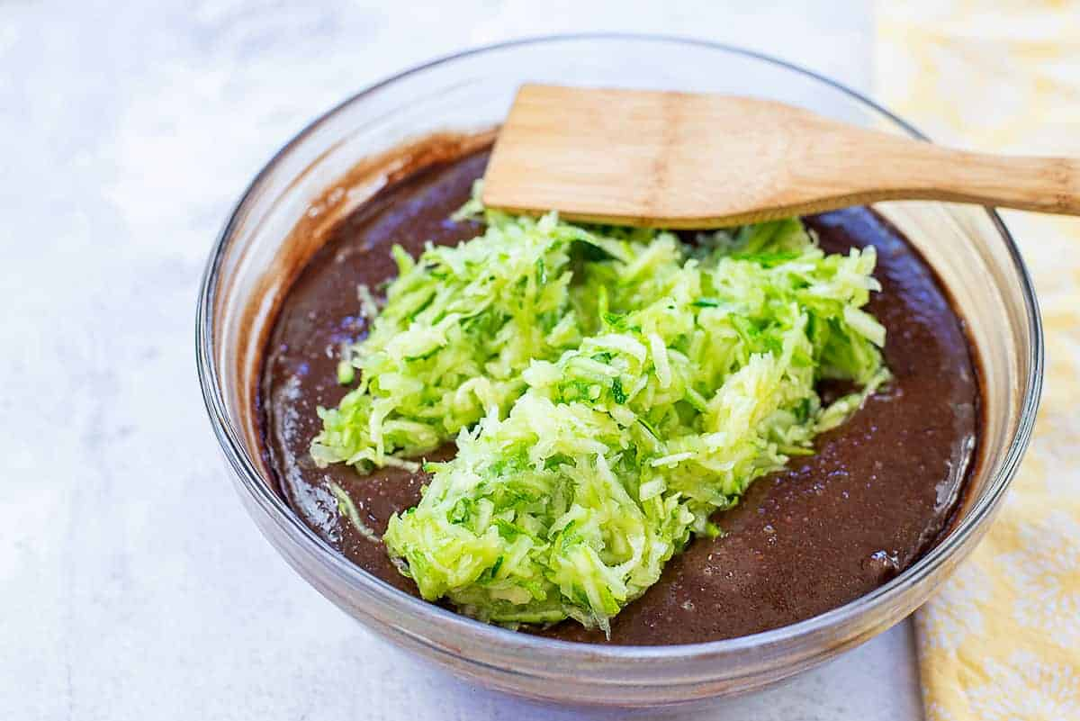 shredded zucchini in bowl of cake batter.