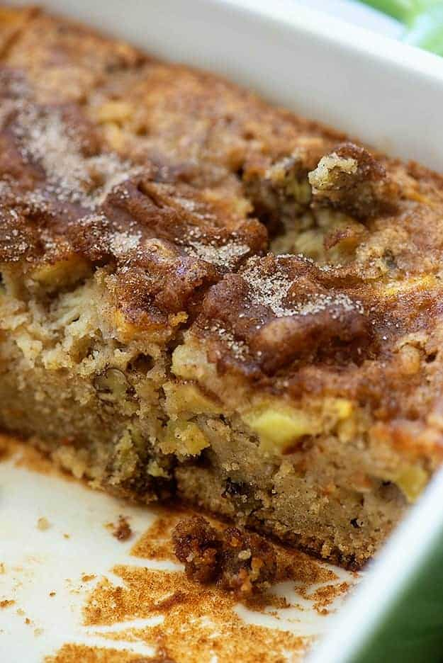 Side view of apple cake in a white cake pan.