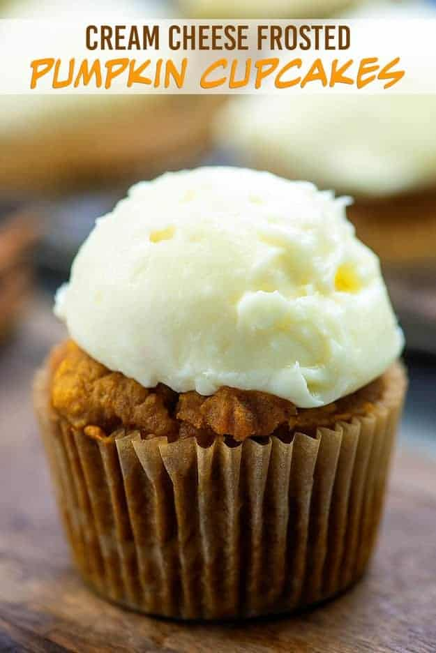 A close up of a wrapped pumpkin cupcake with white frosting on top.