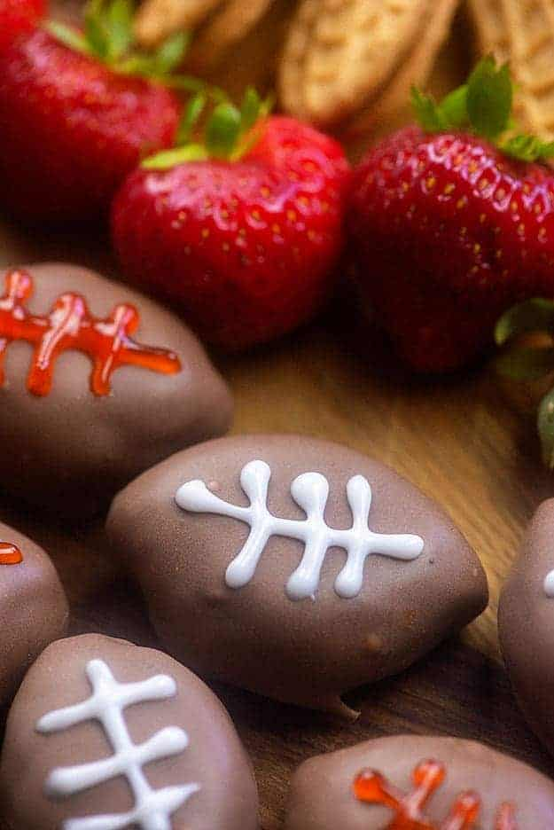Football shaped deserts next to strawberries.