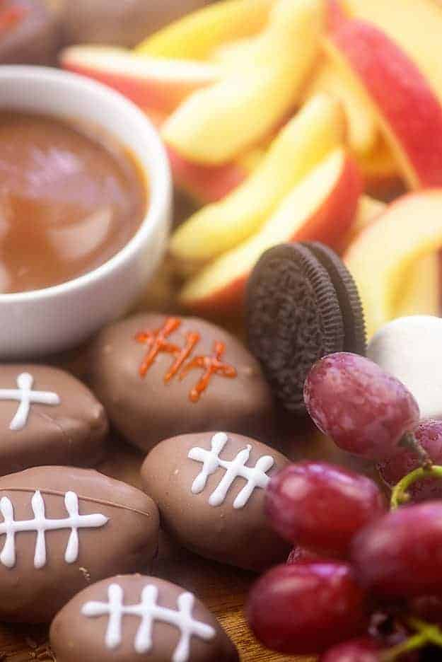 Close up of cookies, grapes, caramel dip, and football-shaped candy.