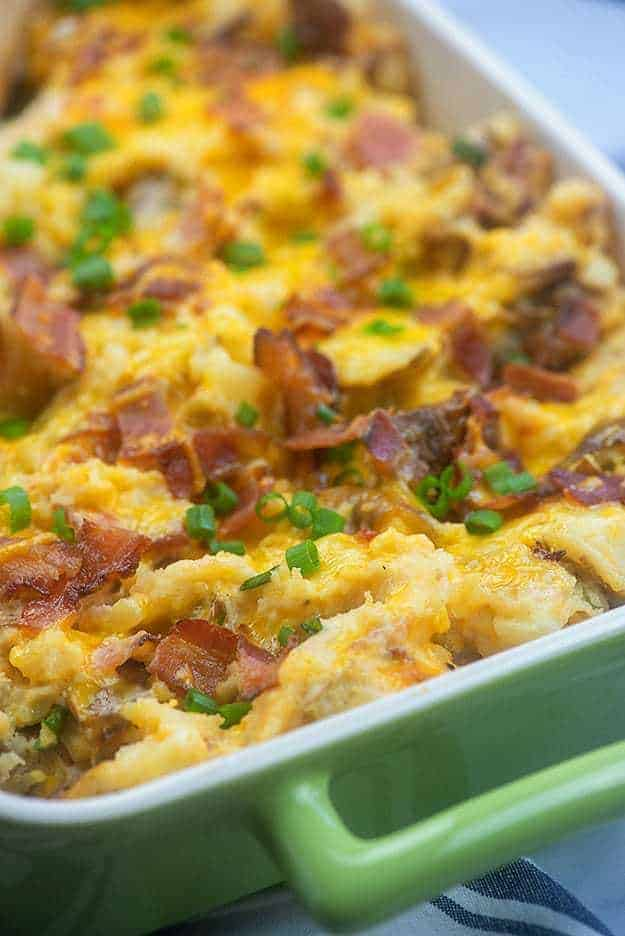 Potatoes topped with cheese and bacon in a baking pan.