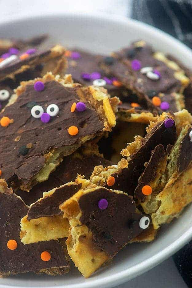 A stack of toffee topped with melted chocolate with a candy face on it.