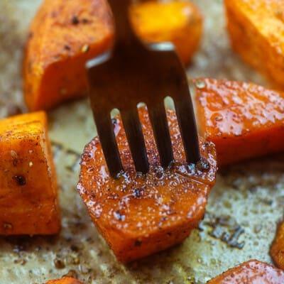 A fork stabbing a sweet potato on a baking sheet.