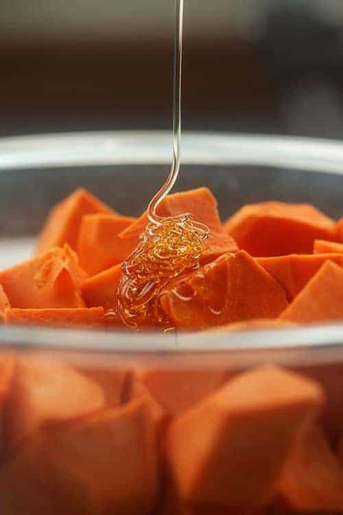Adding honey to sweet potato cubes
