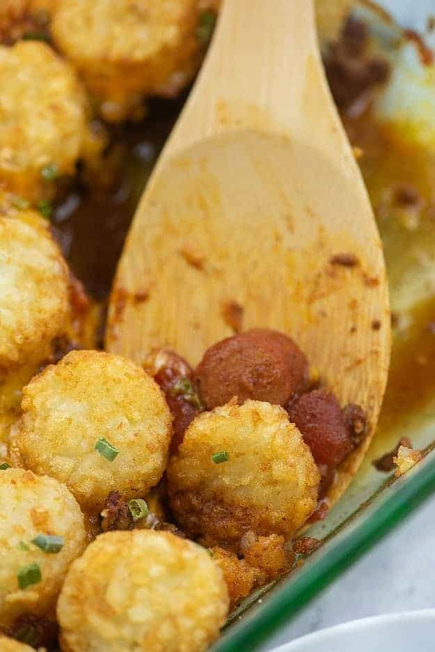 Tater tots and hot dogs on a wooden spoon.