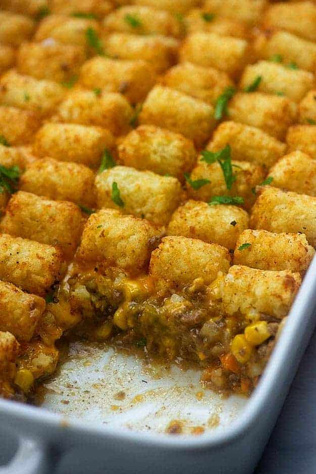 A white baking sheet of tater tots with a serving missing.