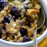Blueberries in oatmeal in a white bowl.