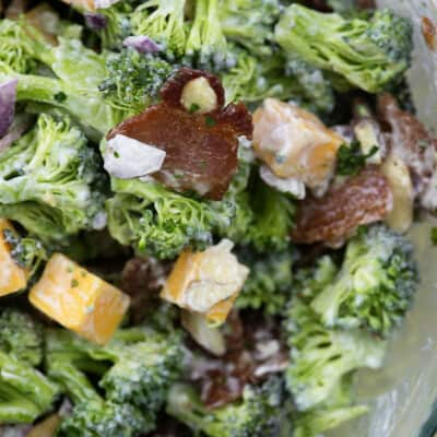 A clear glass bowl of salad with broccoli and bacon pieces.