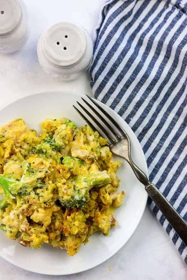 chicken broccoli casserole recipe on white plate with blue striped napkin
