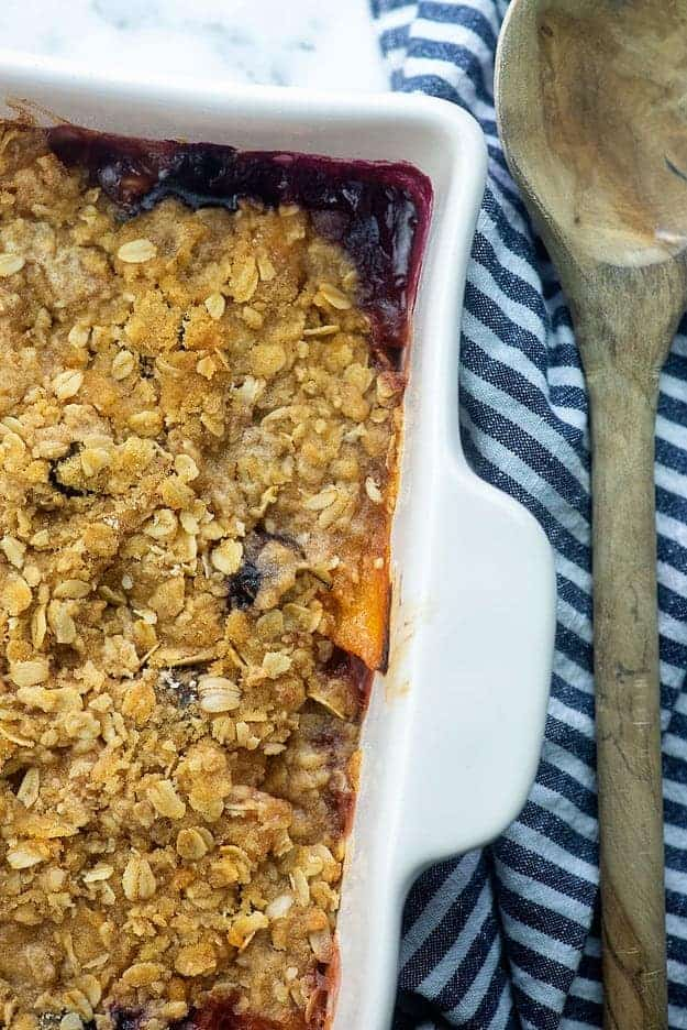 baked peach crisp in white baking dish