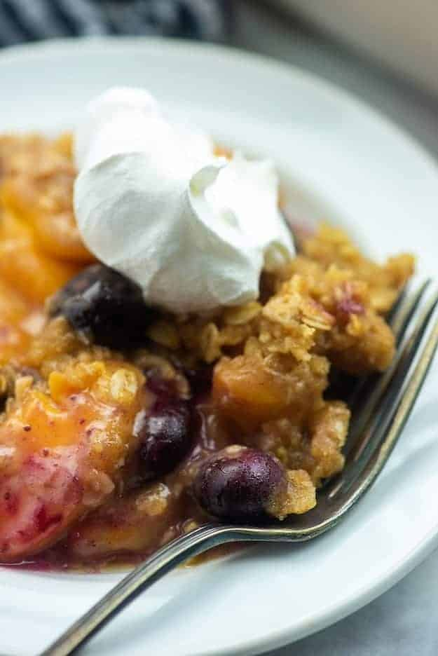 fruit crisp on white plate with whipped cream
