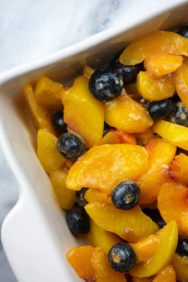 peach and blueberry filling in white baking dish