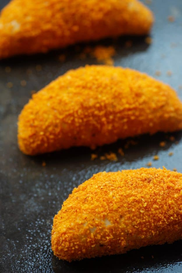 crispy baked chicken taco pockets coated in nacho cheese doritos on baking sheet