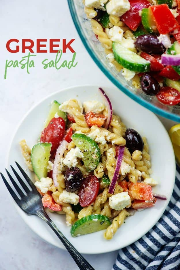 Greek pasta salad on white plate with blue striped napkin