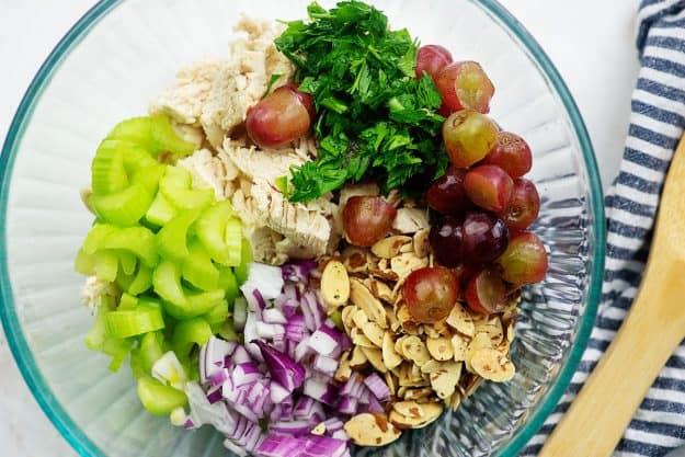 healthy chicken salad ingredients in glass bowl