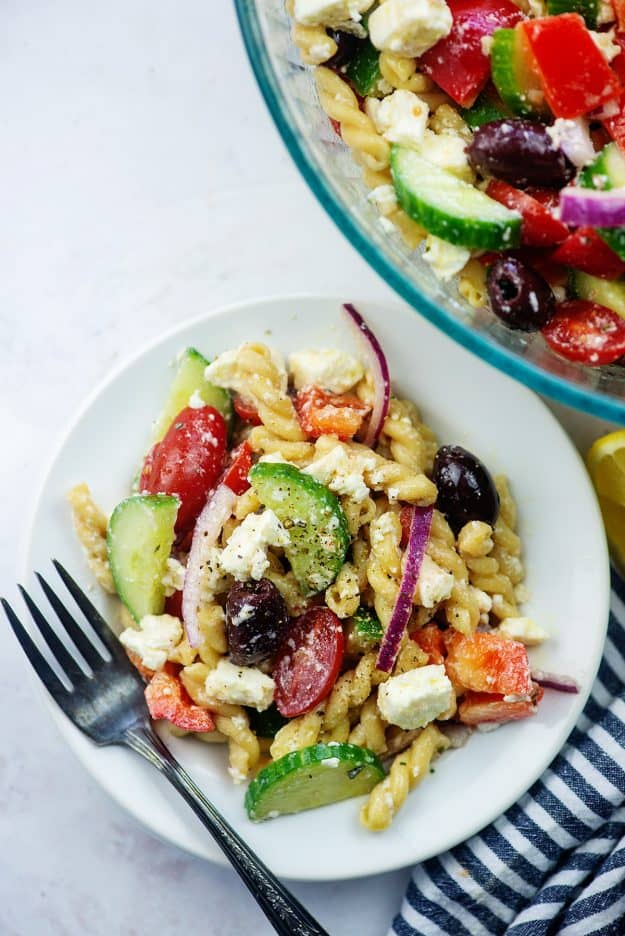 overhead view of Greek pasta salad on white plate.