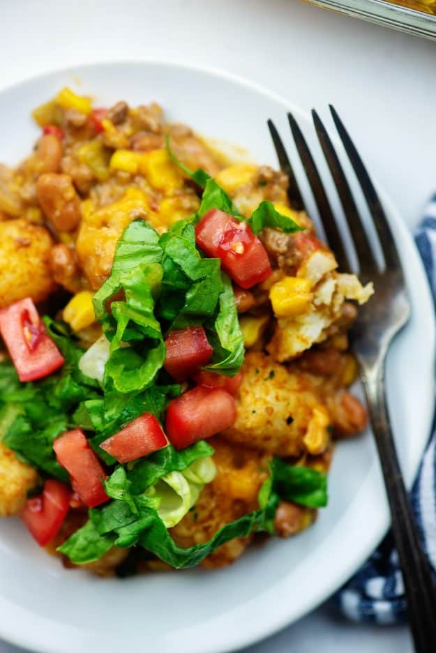 tater tot casserole with lettuce and tomato on white plate