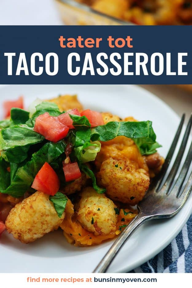 mexican tater tot casserole on white plate with lettuce and tomatoes