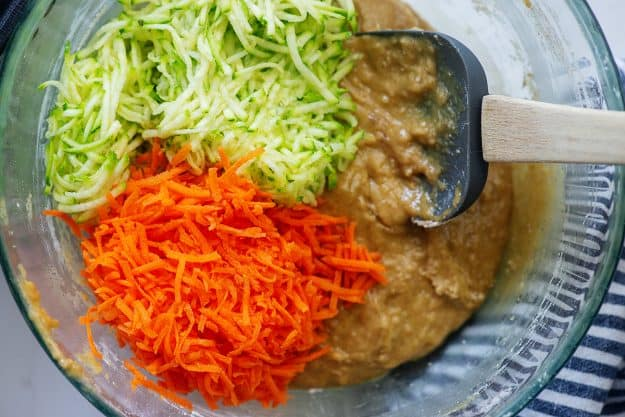 zucchini bread batter with shredded zucchini and carrots in glass mixing bowl