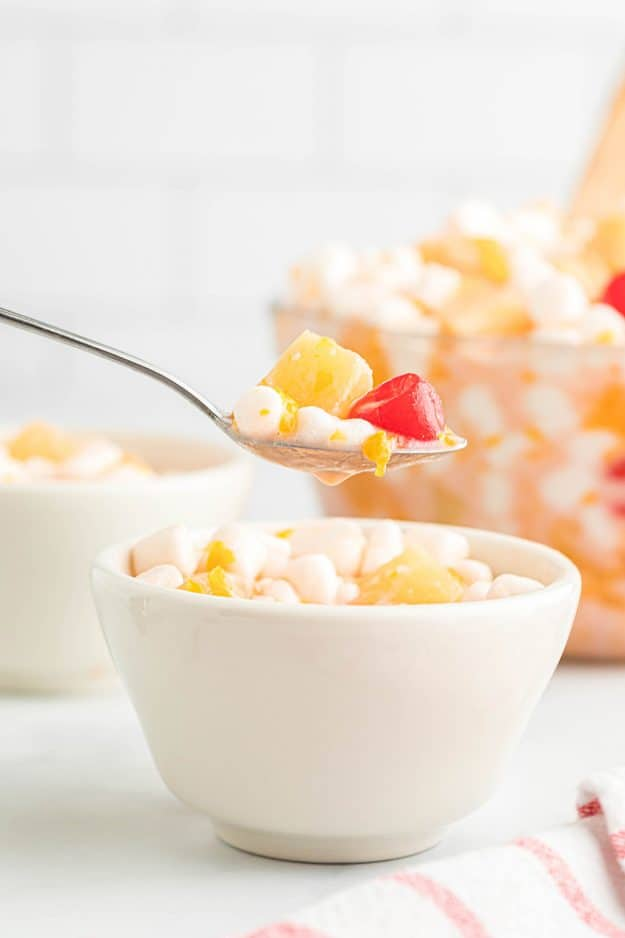 fruit salad with whipped coconut cream in white bowl and on a spoon