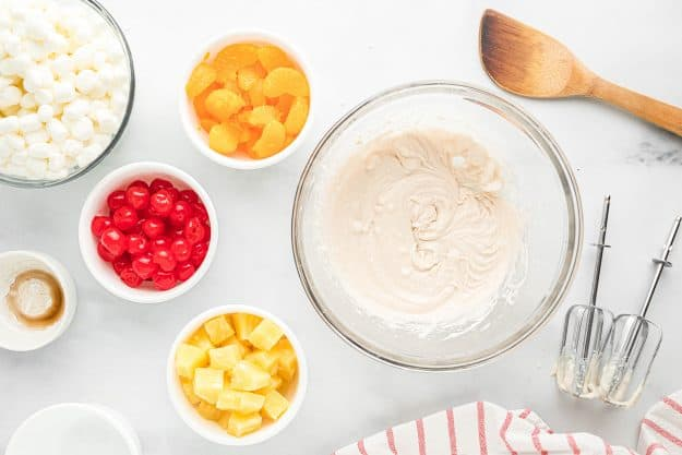 whipped coconut cream in glass bowl surrounded by fruit