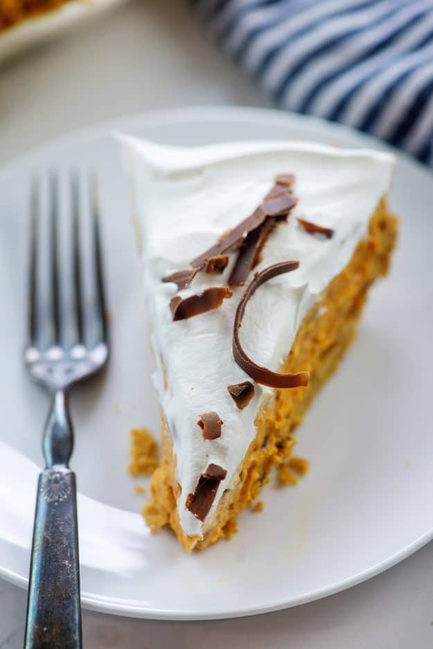 pumpkin chip pie topped with whipped cream on white plate
