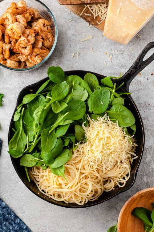 pasta, parmesan, and spinach in cast iron skillet