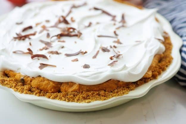 pumpkin pie topped with cool whip and chocolate shavings