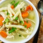 slow cooker chicken noodle soup recipe in white dish surrounded by crackers