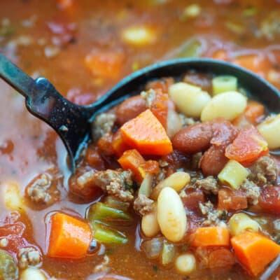 Soup pot with ladle full of pasta fagioli.