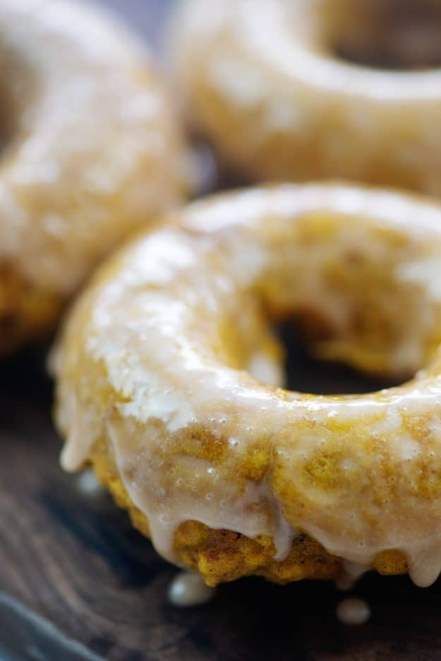 glazed pumpkin donuts on wooden cutting board