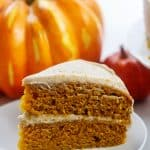 frosted pumpkin layer cake on white plate with pumpkins in the background.