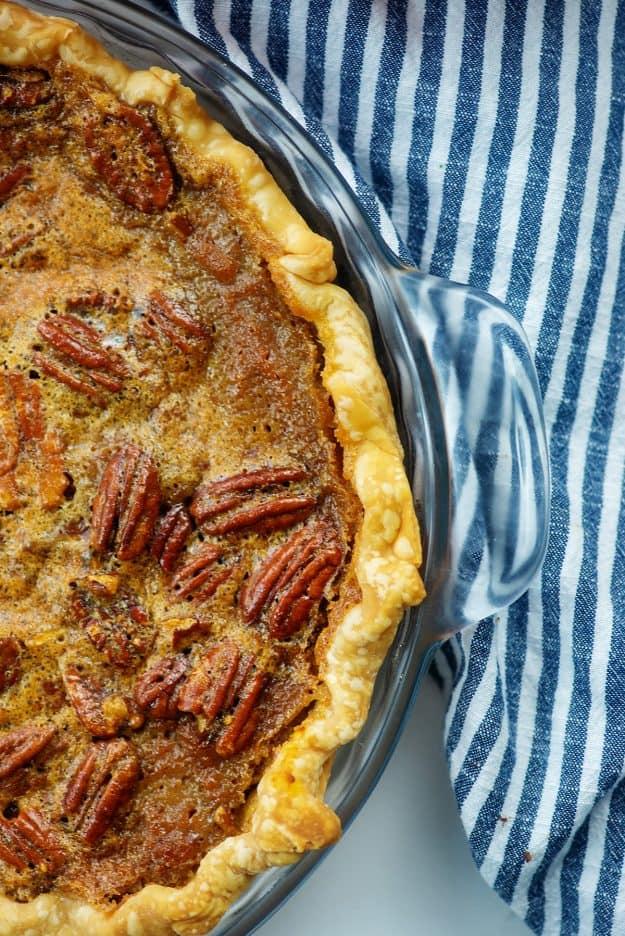 pumpkin pecan pie in glass pie plate with blue striped napkin