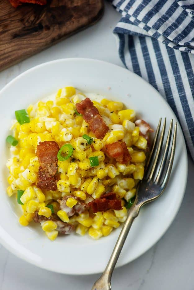 cheesy corn on white plate with fork.