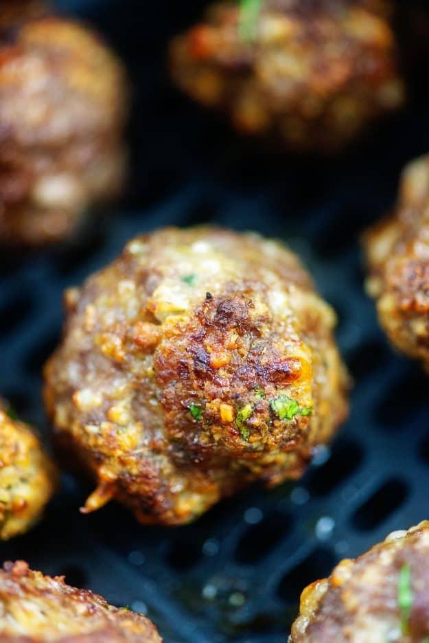 Italian meatballs in air fryer basket.