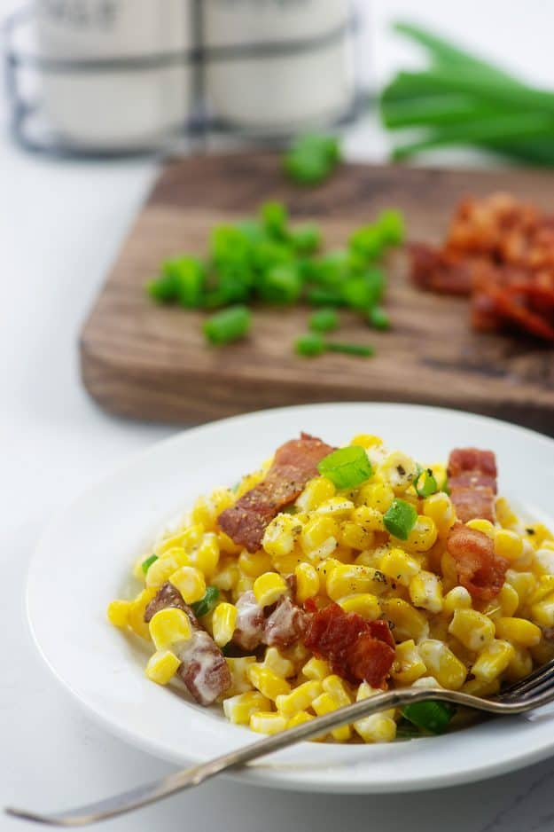 corn with cream cheese on white plate.