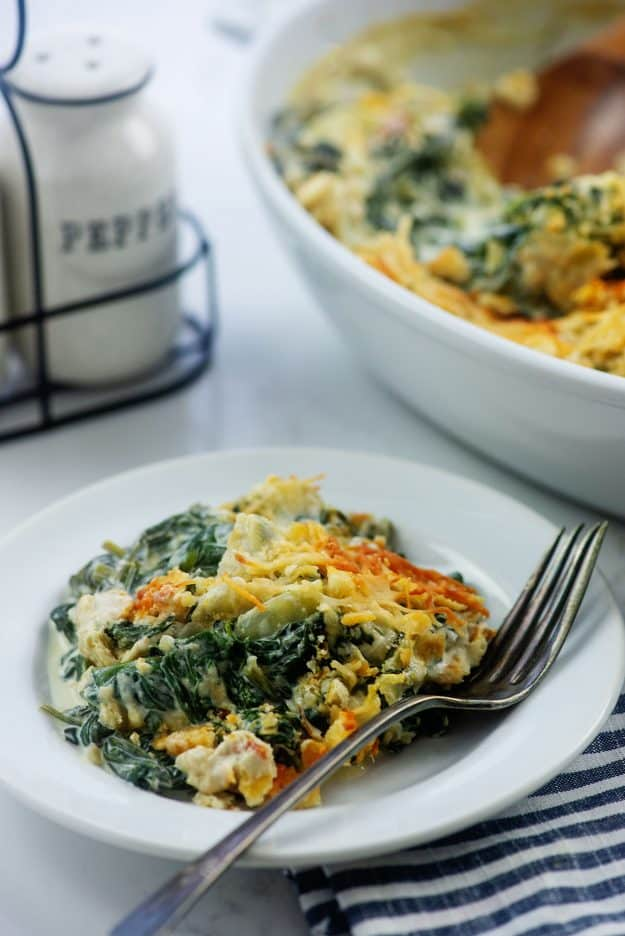 spinach casserole on white plate with vintage fork.