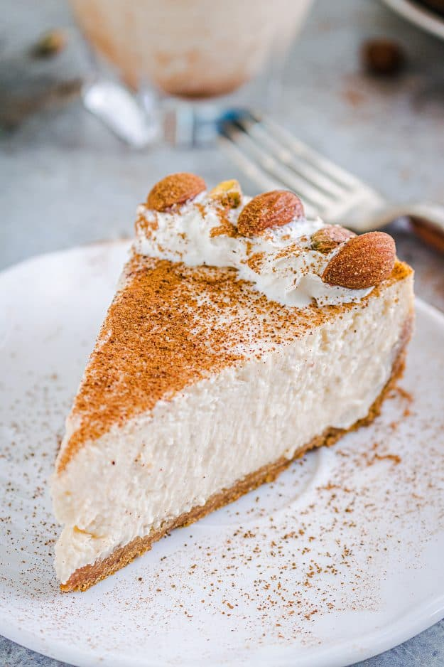 creamy eggnog cheesecake on white plate topped with cinnamon.