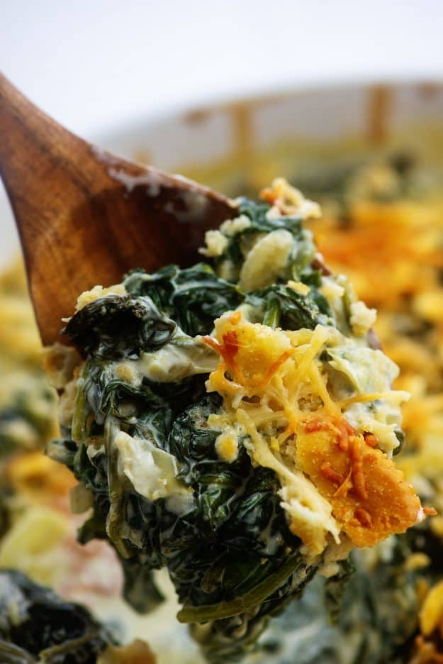 cheesy spinach casserole on wooden spoon.